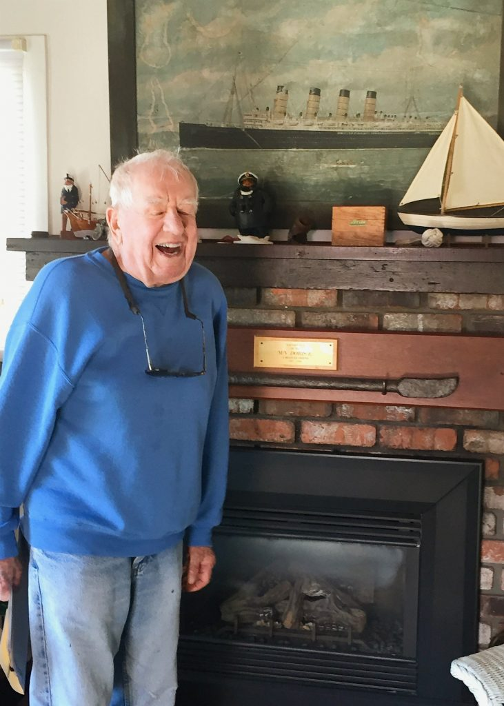Ed pictured in fromt of his fireplace laughing