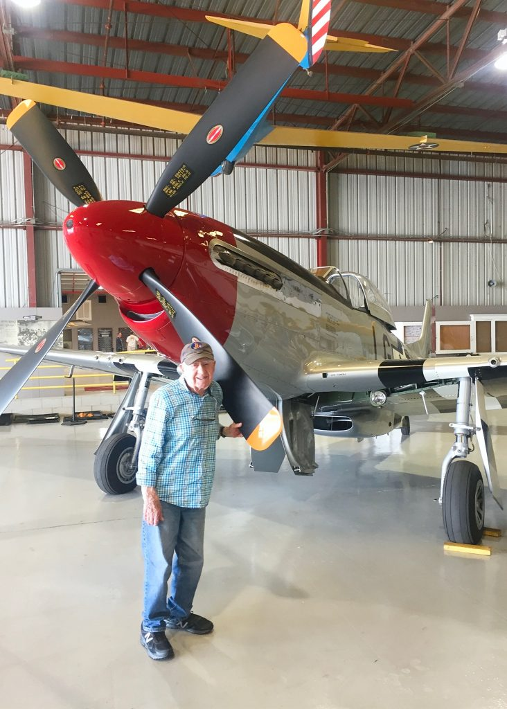 Ed picture in hanger in front of propeller of plane